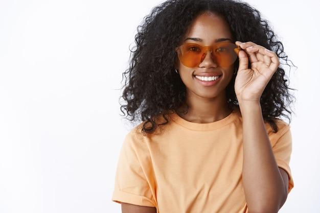 Elegante atraente moderna urbana na moda garota de pele escura usando óculos de sol legais sorrindo encantada e pronta tomando banho de sol perto da piscina maravilhoso clima ensolarado expressando felicidade, alegria, deleite