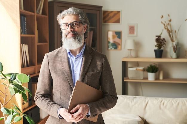 Elegante barbudo profissional envelhecido usando óculos e trajes formais em frente à câmera no fundo das prateleiras e do sofá
