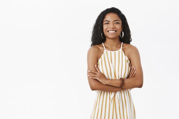 Elegante bem-sucedida encantadora empresária afro-americana com penteado encaracolado em macacão listrado amarelo, cruzando os braços no peito