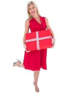 Elegante blonde em vestido vermelho com presente