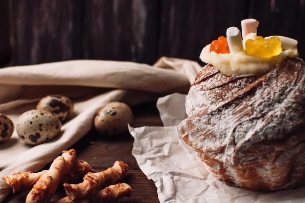 Elegante bolo de páscoa com marshmallows e ursinhos de geléia em papel manteiga em um fundo de madeira.