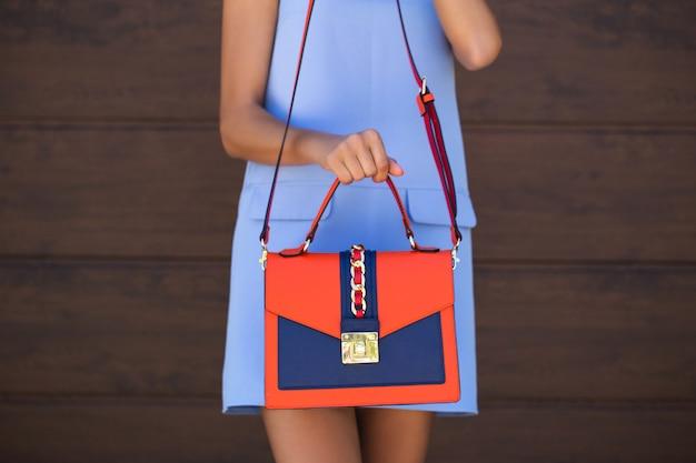 Elegante bolsa feminina de couro azul com couro laranja. a garota segura na mão.