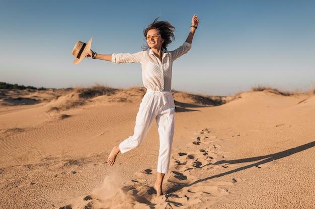 Elegante, bonita e sorridente mulher alegre correndo feliz na areia do deserto, vestida com calça branca e blusa com chapéu de palha no pôr do sol