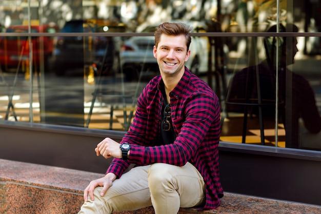 Elegante bonito jovem empresário sentado na rua, sorriso incrível, cabelos castanhos e olhos, vestindo camisa xadrez hipster e calça bege, óculos escuros e relógios, posando perto do restaurante.