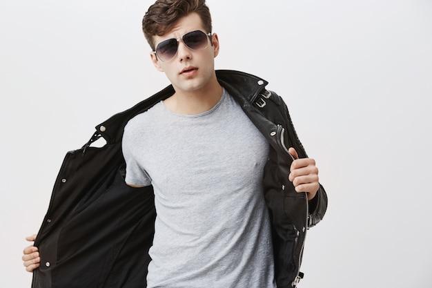 Elegante bonito jovem europeu atraente com corte de cabelo da moda, vestido com jaqueta de couro preta na moda, usando óculos escuros. modelo masculino caucasiano posando dentro de casa.