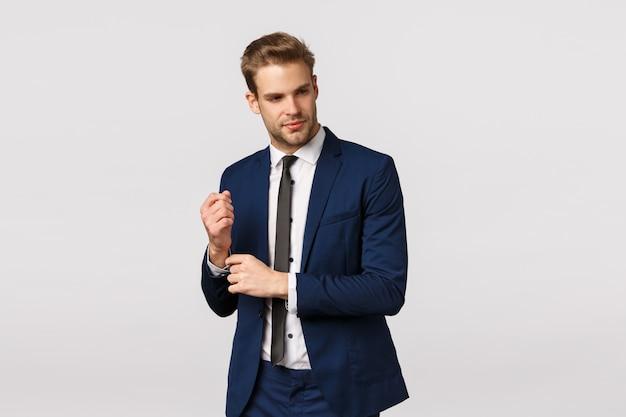 Elegante, bonito, loiro, barbudo, jovem empresário masculino de terno, ajustando as mangas da jaqueta e olhando para longe com um sorriso satisfeito, saborear um bom negócio, sabe como obter sucesso e dinheiro