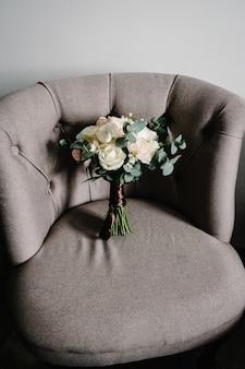 Elegante buquê de flores da noiva em uma poltrona retrô, acessórios do casamento em fundo rústico. composição artesanal tradicional. conceito de férias.