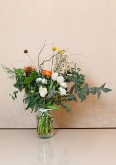 Elegante buquê de flores de inverno arejado de designer está na mesa composta de eucalipto, ranúnculo, tulipas e imortela. vista lateral. horizontal.