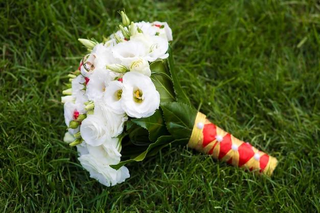 Elegante buquê de flores frescas em um gramado verde. detalhes da decoração do casamento.