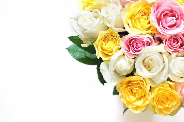 Elegante buquê de muitas rosas lindas no canto, sobre um fundo claro.