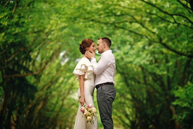 Elegante casal adorável em abraços quentes sob um arco de árvores no parque