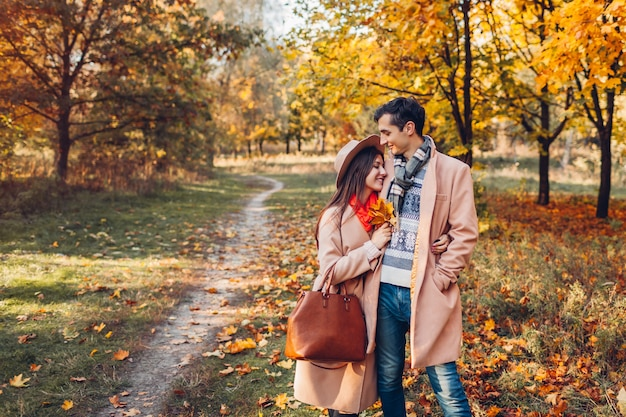 Elegante casal apaixonado caminha no parque outono entre árvores coloridas. homem e mulher felizes se abraçando ao ar livre ao pôr do sol