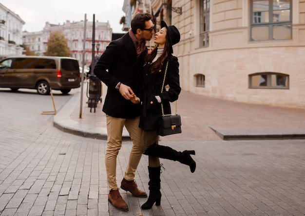 Elegante casal apaixonado, caminhando na rua durante suas férias na europa, se divertindo, beijando, se abraçando. altura toda.