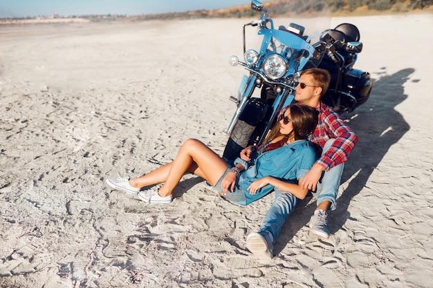 Elegante casal apaixonado posando perto de bicicleta na praia ensolarada.