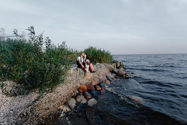 Elegante casal apaixonado sentado à beira-mar junto com dois cães brancos
