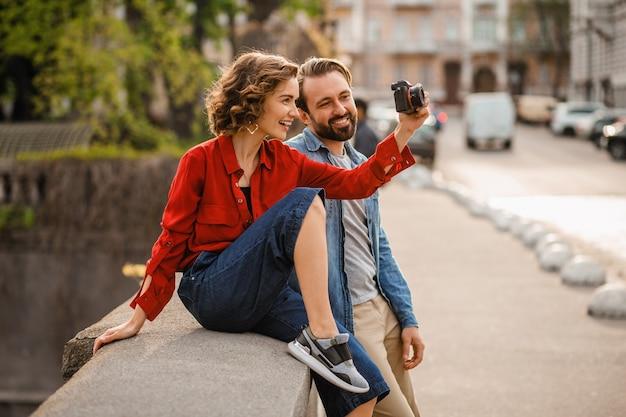 Elegante casal apaixonado, sentado na rua em uma viagem romântica, tirando foto