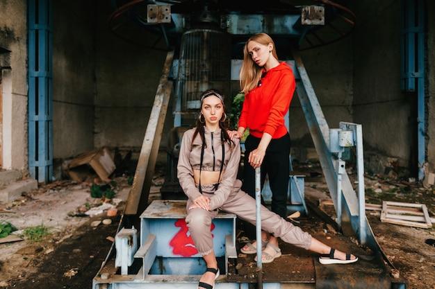 Elegante casal feminino posando na estação de teleférico abandonada.