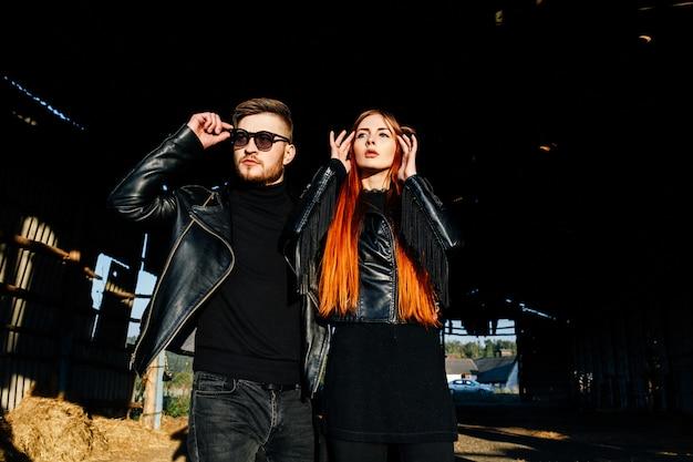 Elegante casal glamourosa em jaquetas de couro preto, posando em um hangar