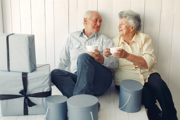 Elegante casal velho sentado em casa com presentes de natal