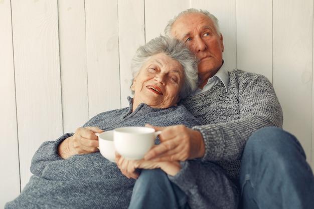 Elegante casal velho sentado em casa em um chão