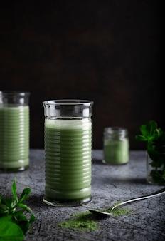 Elegante chá verde matcha em um copo transparente com uma colher sobre uma mesa de mármore escuro e fundo preto