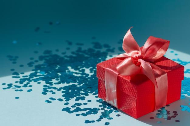 Elegante composição festiva com uma caixa de presente vermelha com um laço de cetim coral e confetes polvilhados azuis. decoração de natal na moda.