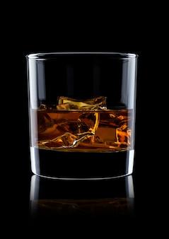 Elegante copo de uísque com cubos de gelo no fundo preto com reflexão