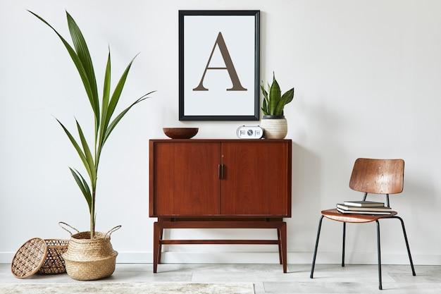 Elegante design de interiores de sala de estar com cômoda retro de madeira, cadeira, planta tropical em cesta de vime, decoração e acessórios pessoais elegantes. moldura na parede branca ..