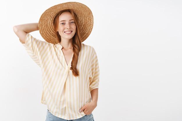 Elegante e alegre garota ruiva atraente com sardas segurando a mão atrás de um boné de palha e sorrindo amplamente, tendo uma ótima manhã caminhando na praia
