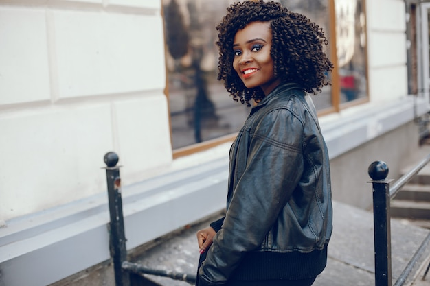 Elegante e elegante garota de pele escura com cabelo encaracolado andando pela cidade de verão