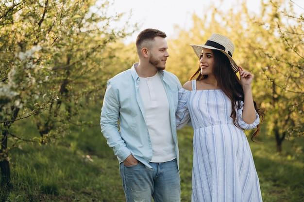 Elegante e elegante mulher grávida e seu marido vestiram um tom branco e azul pastel no jardim por do sol