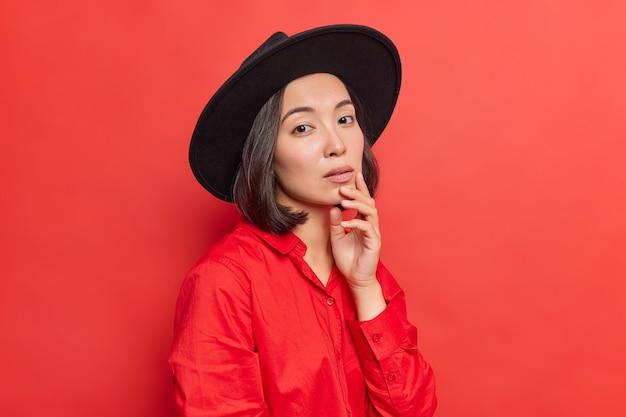 Elegante e encantadora jovem asiática mantém a mão no queixo com expressão séria e confiante tem cabelo escuro natural, pele saudável usa chapéu preto, camisa vermelha posa brilhante