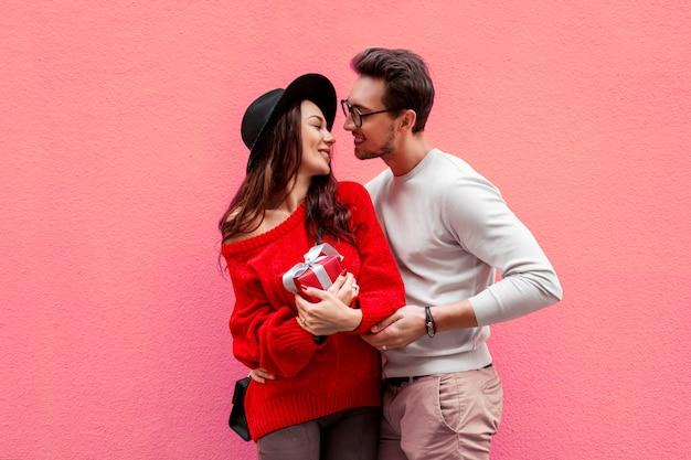 Elegante elegante casal apaixonado, de mãos dadas e olhando um ao outro com prazer. mulher de cabelos longos na camisola de malha vermelha com o namorado dela posando.
