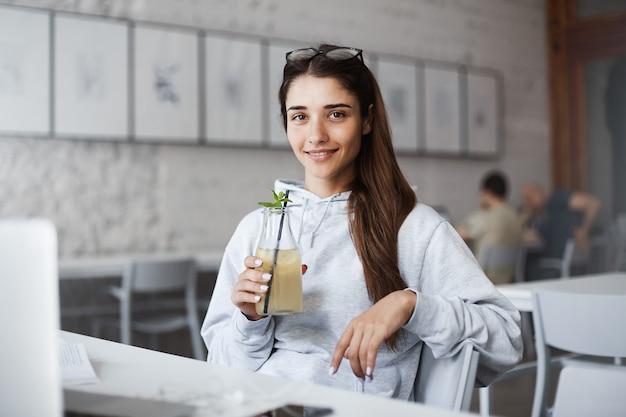 Elegante elegante jovem estudante no café, bebendo um coquetel e sorrindo amplamente, durante uma pausa do trabalho que ela faz através do computador portátil.