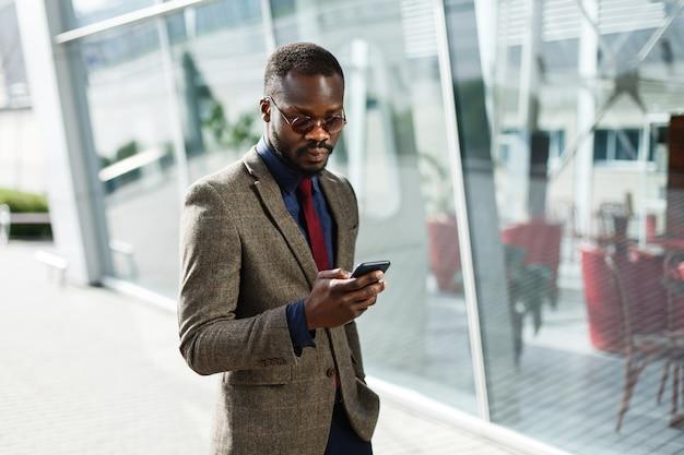 Elegante empresário afro-americano negro trabalha em seu smartphone