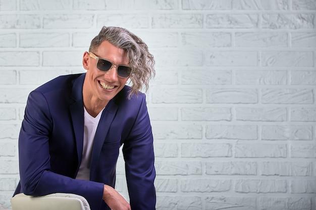 Elegante empresário com cabelo comprido encaracolado em óculos de sol, sentado na cadeira em branco