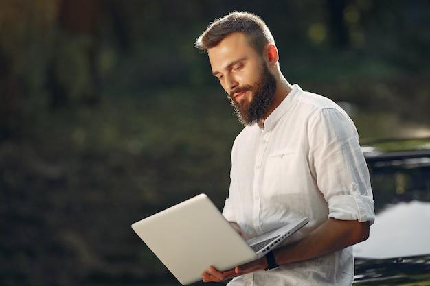 Elegante empresário de pé perto do carro e use o laptop