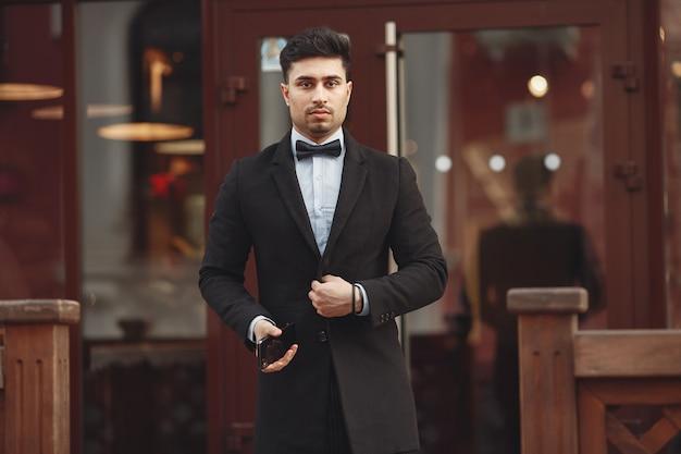 Elegante empresário em um terno preto do lado de fora