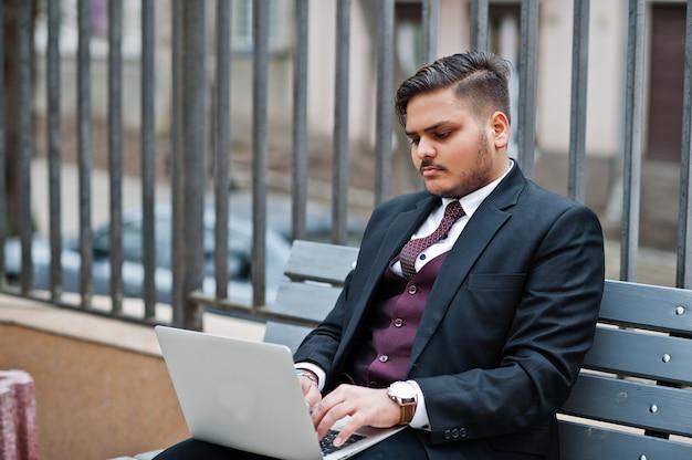 Elegante empresário indiano com roupa formal, sentado no banco com o laptop.