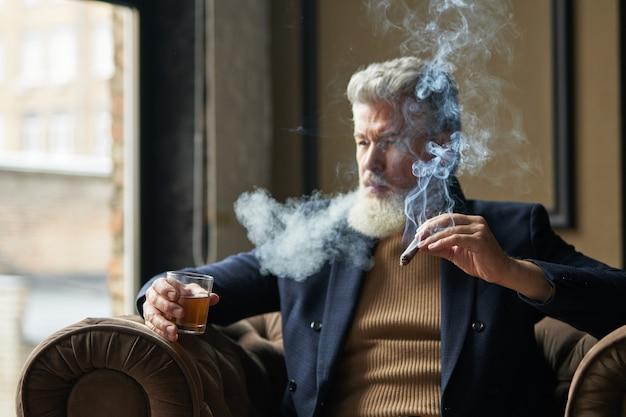 Elegante empresário maduro fumando charuto com fumaça e segurando um copo de uísque enquanto relaxa