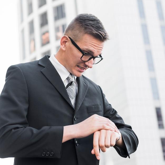 Elegante empresário, olhando para o relógio