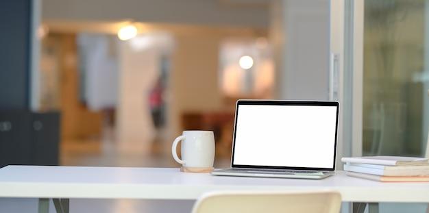 Elegante escritório em casa com o laptop de tela aberta em branco