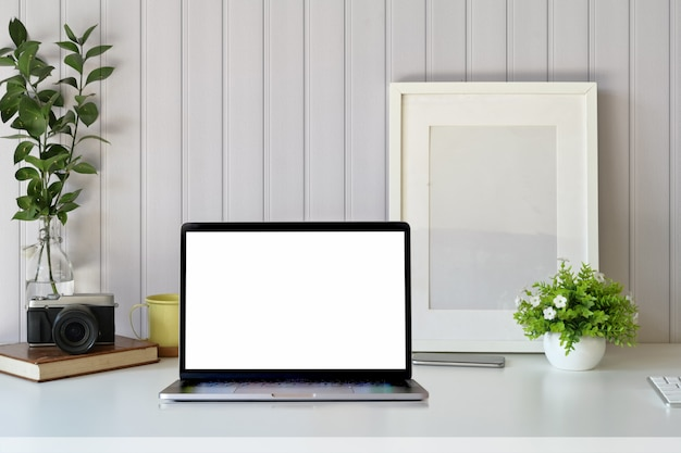 Elegante espaço de trabalho com computador portátil, suprimentos criativos, planta de casa e livros no escritório.