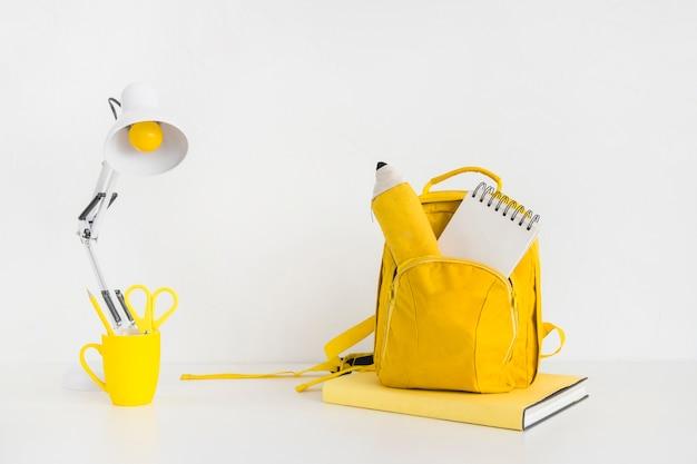 Elegante espaço de trabalho na adolescência com mochila amarela e lâmpada de leitura