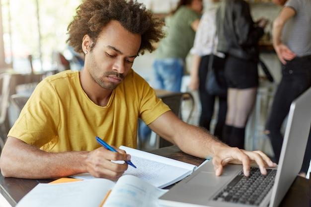 Elegante estudante masculino sentado no restaurante na mesa de madeira, escrevendo algo em seu livro de cópia, digitando no teclado de seu laptop, olhando seriamente para baixo. preparação para exames ou aulas