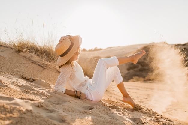 Elegante feliz atraente sorridente mulher posando no deserto vestida com roupas brancas, chapéu de palha e óculos escuros no pôr do sol