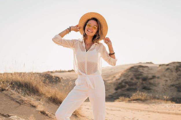 Elegante, feliz e atraente mulher sorridente posando na areia do deserto, vestida com roupas brancas, chapéu de palha e óculos escuros no pôr do sol, dia ensolarado de verão
