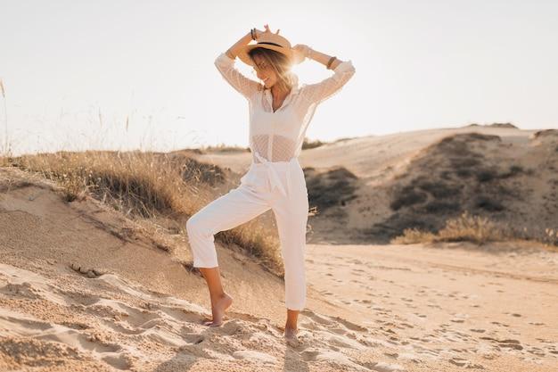 Elegante, feliz e atraente mulher sorridente posando na areia do deserto, vestida com roupas brancas, chapéu de palha e óculos escuros no pôr do sol