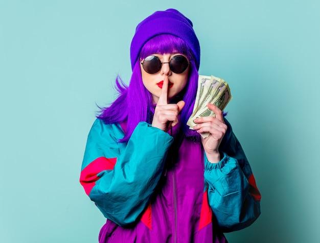 Elegante garota branca com cabelo roxo e agasalho esportivo segurando dinheiro na parede azul