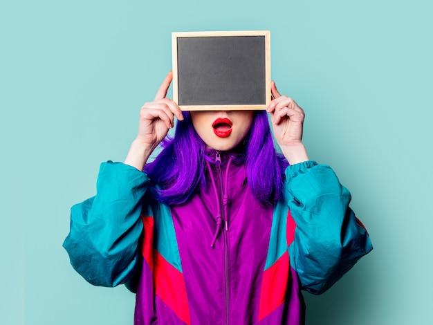Elegante garota branca com cabelo roxo e agasalho segurando prancha na parede azul